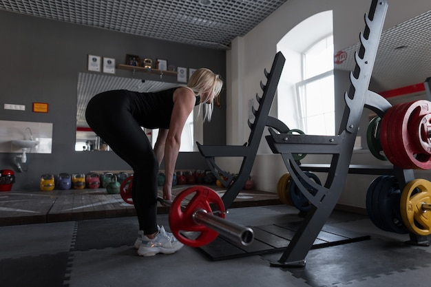 Młoda kobieta robi ciężkie ćwiczenia na siłowni ze sztangą. dziewczyna w świetnej formie robi przysiady w studio fitness