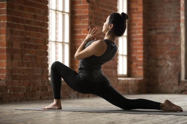 Młoda kobieta robi ćwiczenia anjaneyasana
