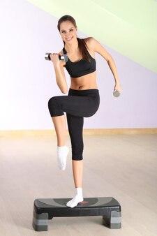Młoda kobieta robi ćwiczenia fitness na stepperze w gimnazjum