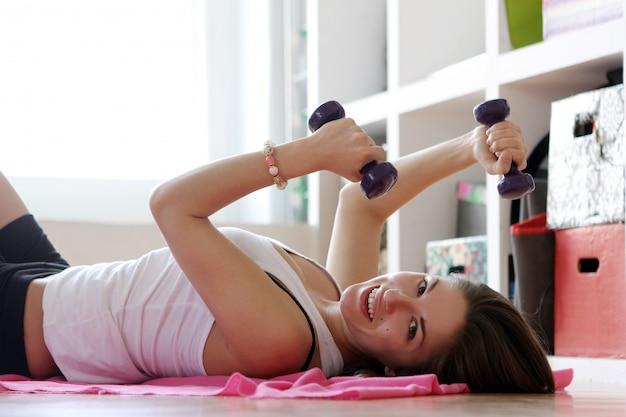 Młoda kobieta robi ćwiczenia gimnastyczne
