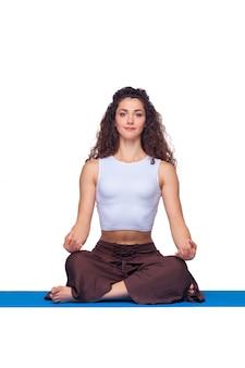 Młoda kobieta robi ćwiczenia jogi na białym tle