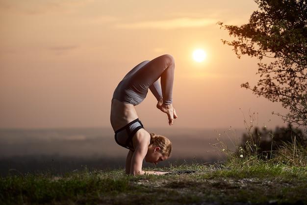 Młoda kobieta robi ćwiczenia jogi na świeżym powietrzu o zachodzie słońca