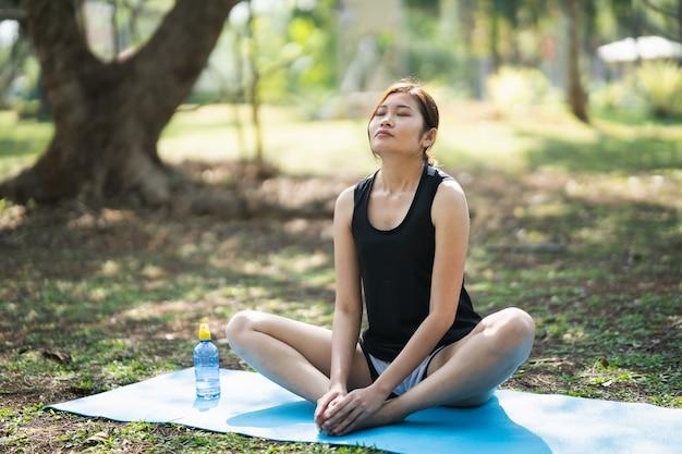 Młoda kobieta robi ćwiczenia jogi na świeżym powietrzu w parku, koncepcja jogi sport
