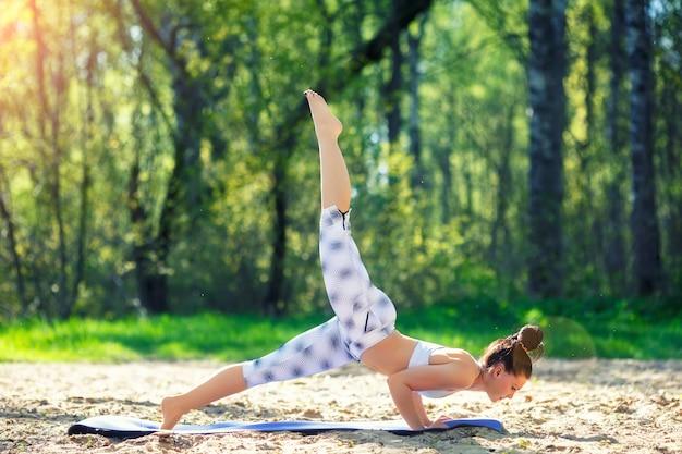 Młoda kobieta robi ćwiczenia jogi w parku miejskim lato