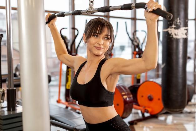 Młoda kobieta robi ćwiczenia na ramiona
