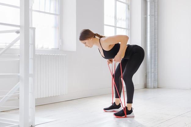Młoda kobieta robi ćwiczenia oporowe wioślarza z paskiem mocy w widoku z boku w wysokiej siłowni