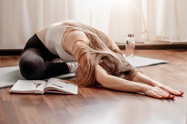 Młoda kobieta robi ćwiczenia pilates siedząc na macie do jogi na podłodze w domu. sporty rozciągające. joga w domu