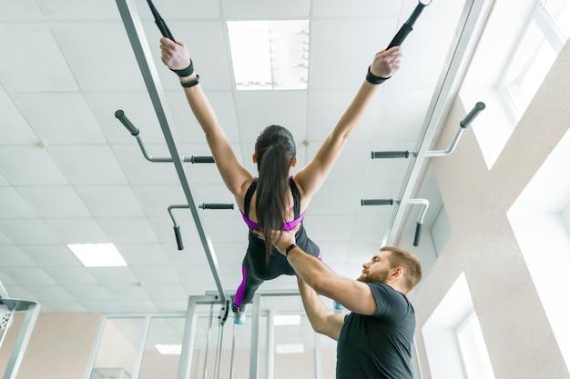 Młoda kobieta robi ćwiczenia rehabilitacyjne z osobistym instruktorem