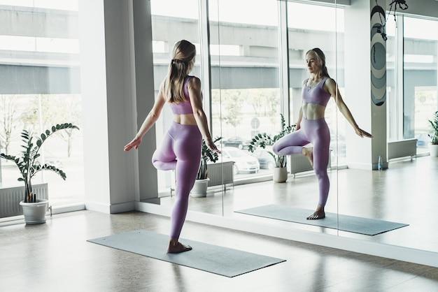 Młoda kobieta robi ćwiczenia rozciągające przez lustro na macie w jasnej sali jogi.