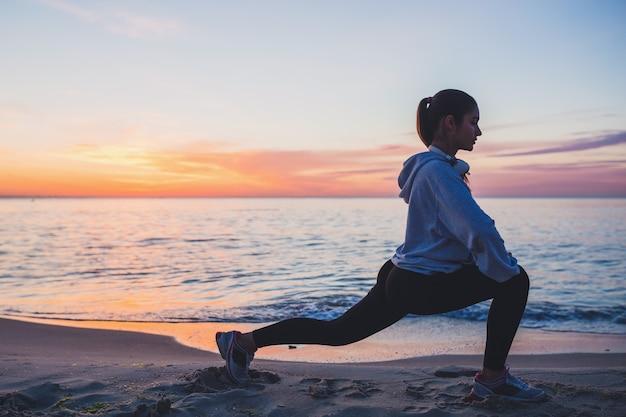 Młoda kobieta robi ćwiczenia sportowe na plaży o wschodzie słońca w godzinach porannych