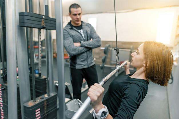 Młoda kobieta robi ćwiczeniom z osobistym instruktorem w gym