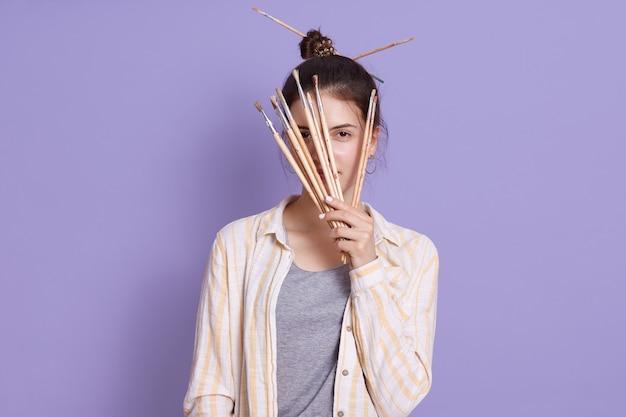 Młoda kobieta robi fryzurę za pomocą pędzli malarskich, trzymając pędzle w dłoniach i zasłaniając jej twarz
