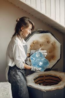 Młoda kobieta robi garncarstwu w warsztacie