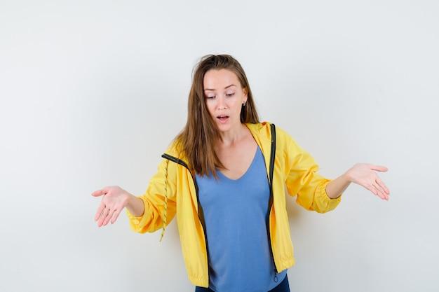 Młoda kobieta robi gest powitalny w koszulce, kurtce i patrząc skupiony, widok z przodu.
