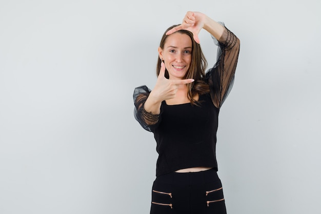 Młoda kobieta robi gest ramy w czarnej bluzce i patrząc wesoło. przedni widok. miejsce na tekst