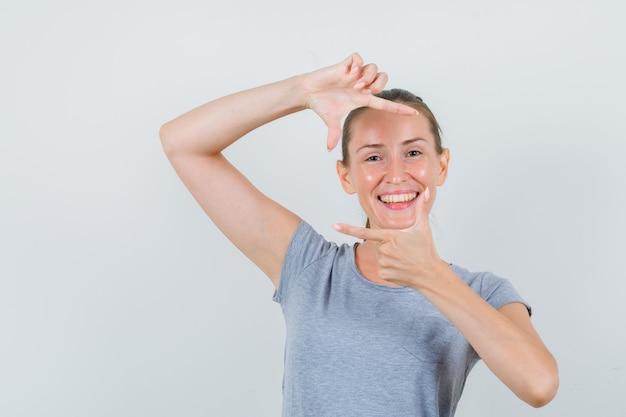 Młoda kobieta robi gest ramy w szarej koszulce i wygląda radośnie. przedni widok.