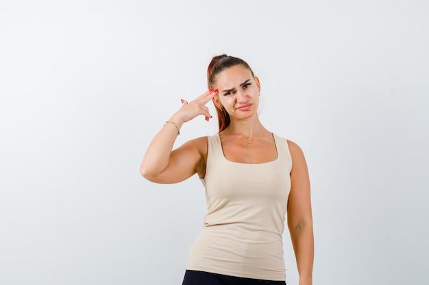 Młoda kobieta robi gest samobójczy w beżowym bezrękawniku i wygląda beznadziejnie, widok z przodu.