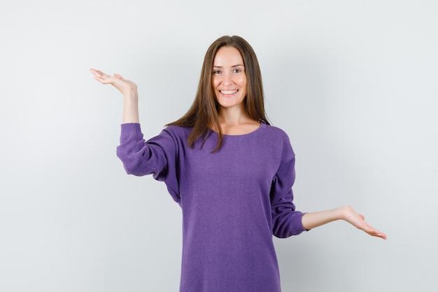 Młoda kobieta robi gest wagi w fioletowej koszuli i szuka szczęśliwy. przedni widok.