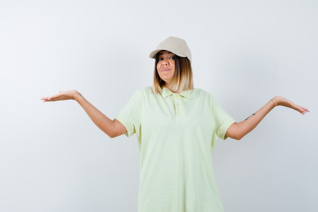 Młoda kobieta robi gest wagi w t-shirt, czapce i szuka pewności siebie. przedni widok.