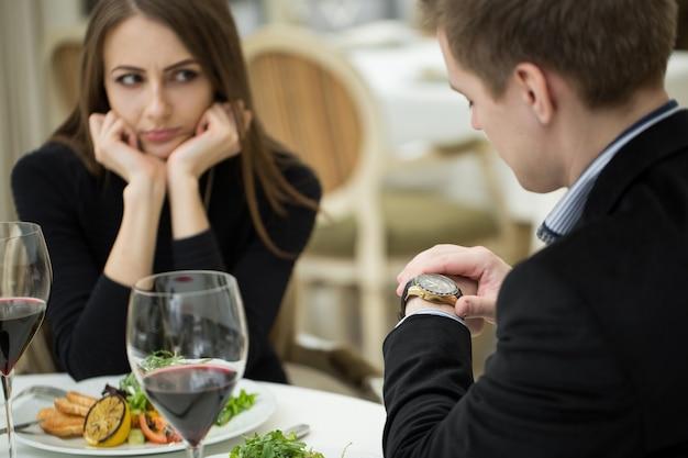Młoda kobieta robi gest zirytowanego wyrażenia na złą randkę w restauracji. mężczyzna patrzy na zegarek