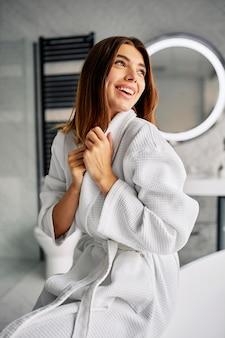 Młoda kobieta robi jej rutynowej pielęgnacji skóry rano