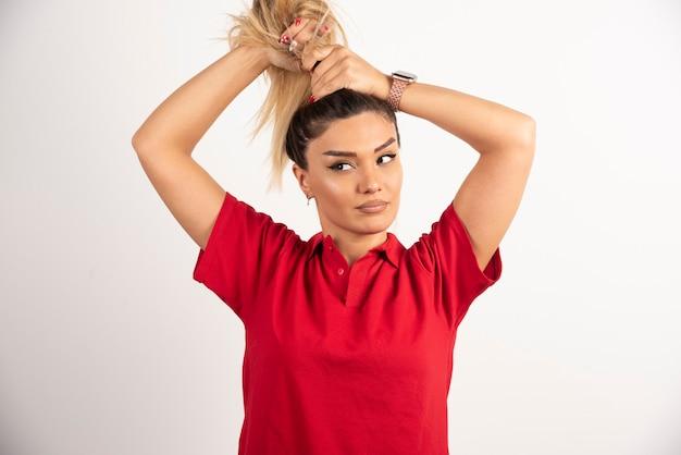 Młoda kobieta robi jej włosy na białym tle.