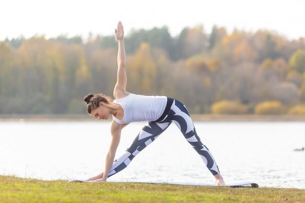 Młoda kobieta robi joga blisko jeziora outdoors, medytacja. fitness sportowy i ćwiczenia w przyrodzie. jesienny zachód słońca.