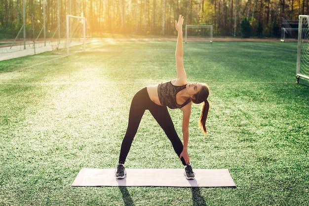 Młoda kobieta robi joga lub fitness na stadionie