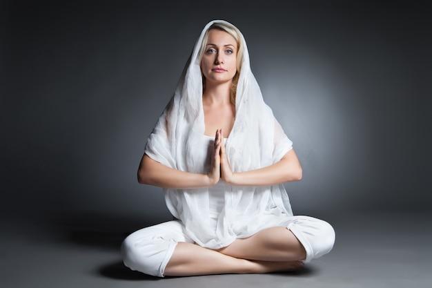 Młoda kobieta robi joga na białym tle na ciemnym tle