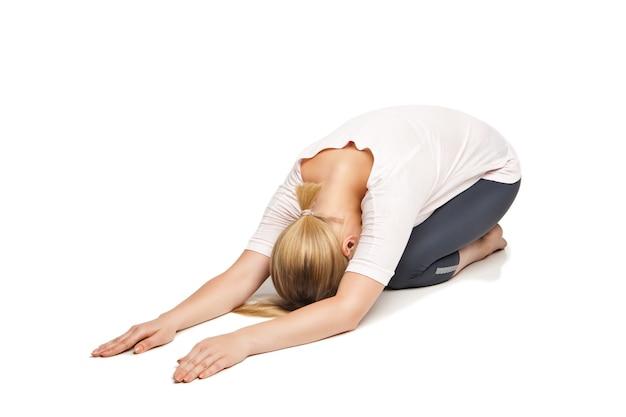 Młoda kobieta robi joga na białym tle