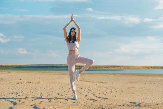 Młoda kobieta robi joga na plaży