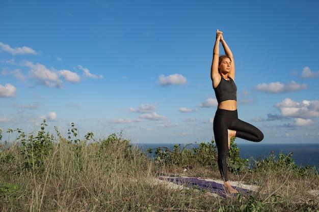 Młoda kobieta robi joga na świeżym powietrzu z niesamowitym widokiem z tyłu. bali. indonezja.