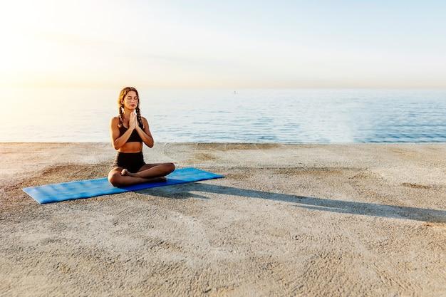 Młoda kobieta robi joga nad morzem. pozycja sukhasany