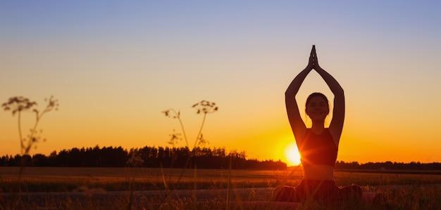 Młoda kobieta robi joga o zachodzie słońca w lecie