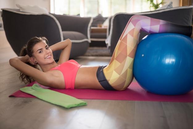 Młoda kobieta robi joga w domu. jeśli chcesz być w formie, musisz ćwiczyć