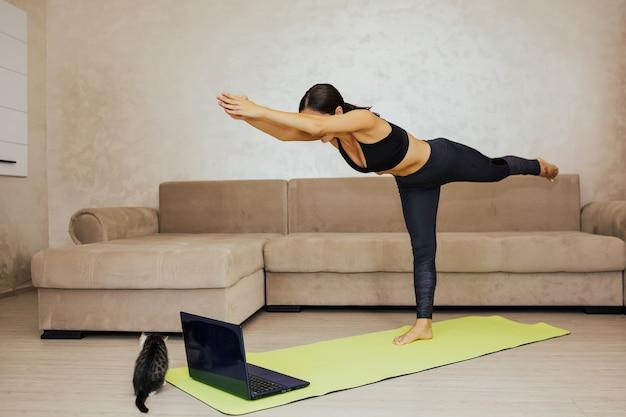 Młoda kobieta robi joga w domu. praktykuje jogę, wykonuje ćwiczenia warrior iii, pozy virabhadrasana 3