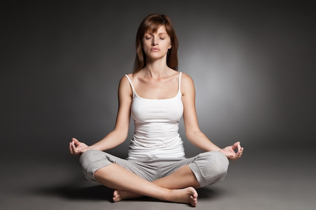 Młoda kobieta robi jogę na ciemnym tle