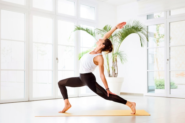 Młoda kobieta robi jogi ashta chandrasana