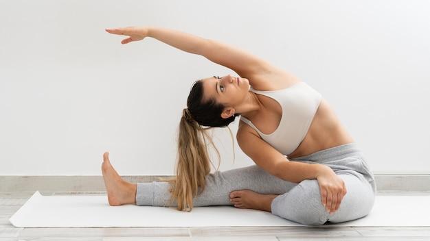Młoda kobieta robi jogi na białej macie
