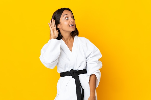 Młoda kobieta robi karate na białym tle na żółtym tle, słuchając czegoś, kładąc rękę na uchu