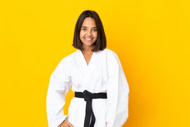 Młoda kobieta robi karate na białym tle na żółtym tle, śmiejąc się