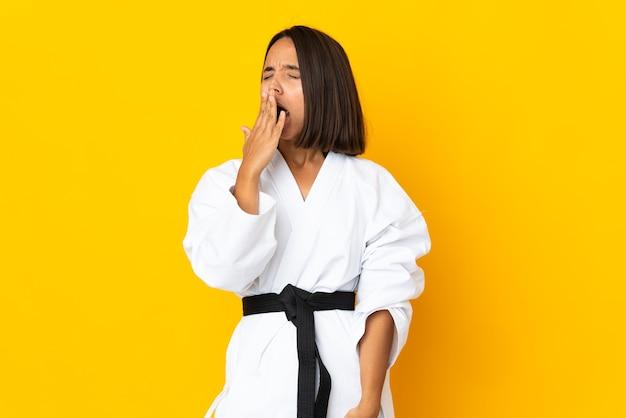 Młoda kobieta robi karate na białym tle