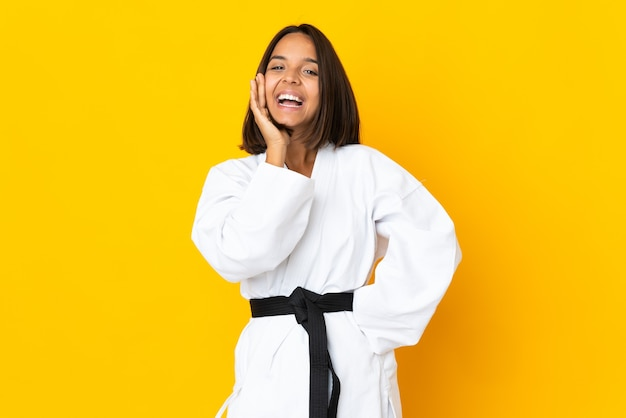 Młoda kobieta robi karate na żółtym tle krzycząc z szeroko otwartymi ustami