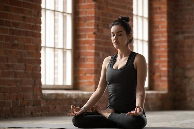 Młoda kobieta robi lotosu ćwiczeniu