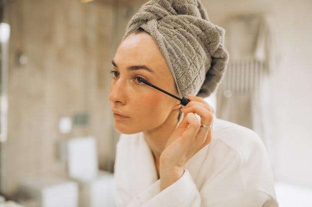 Młoda kobieta robi makijaż i nakłada tusz do rzęs