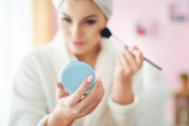 Młoda kobieta robi makijaż rano