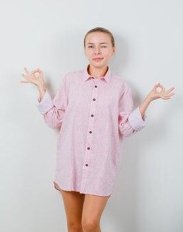 Młoda kobieta robi medytację i mrugając okiem w różowej koszuli