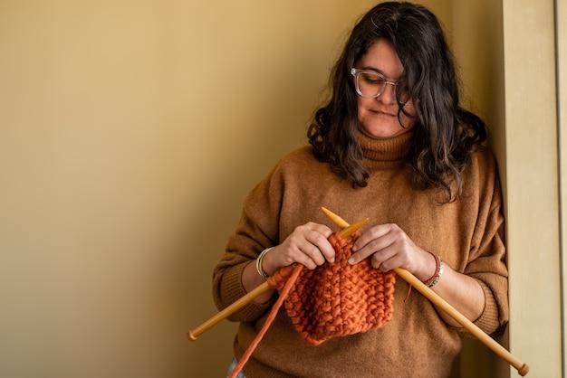 Młoda kobieta robi na drutach sweter w domu, aby ogrzać się zimą. skopiuj miejsce