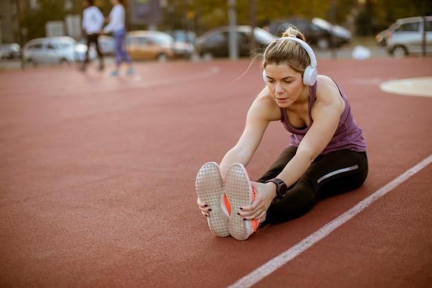 Młoda kobieta robi niektóre ćwiczenia i streching nogi przy sądem przy plenerowym