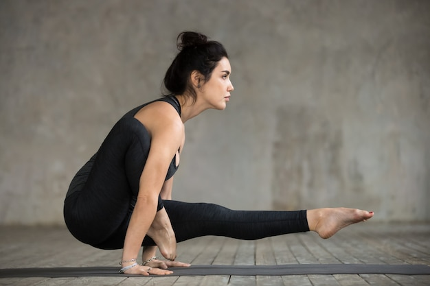 Młoda kobieta robi noga przez ramię ćwiczenia